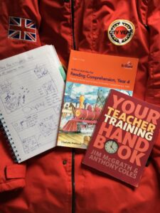 Teacher training handbook, reading workbook, and notebook on top of a CYUK red jacket