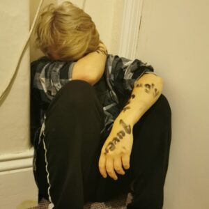 Boy looking upset with his elbow covering his face