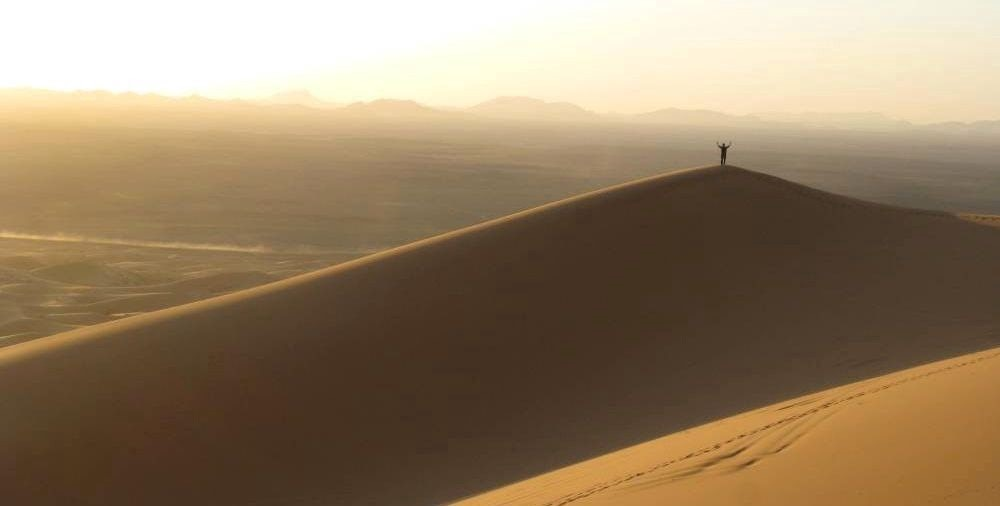 Person on top of a sand dune