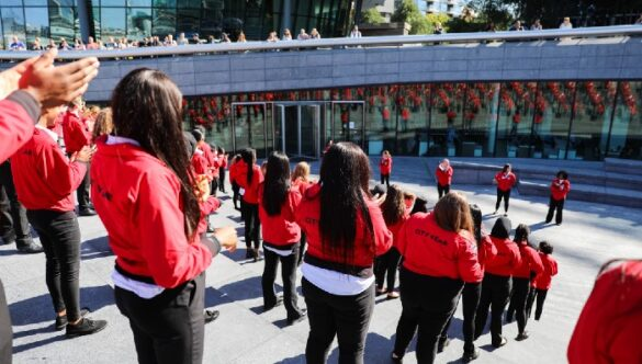 Volunteer mentors in red jackets on the steps of City Hall in London on Opening Day